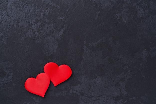 Два красных сердца на черном фоне. вид сверху