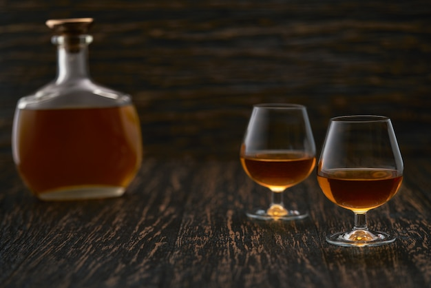 Два бокала бренди или коньяка и бутылка на деревянном столе.