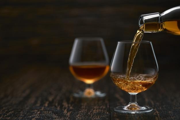 Лить коньяк из бутылки в стакан с деревянным столом.