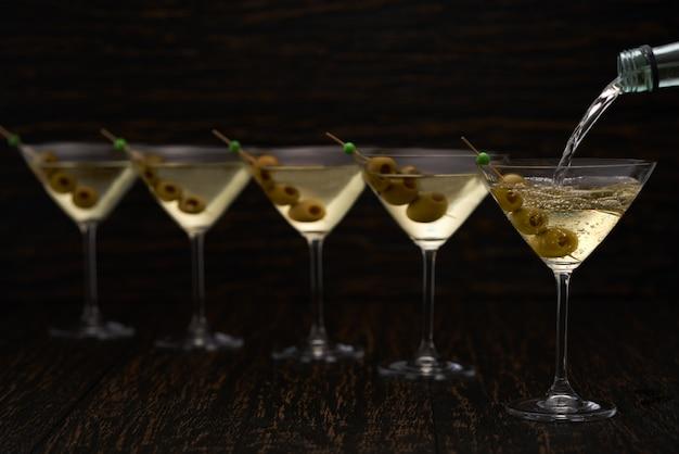 Лить алкогольный напиток из бутылки в стакан с деревянным столом.