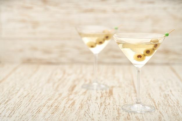 Два коктейля с алкогольными напитками и зелеными оливками.