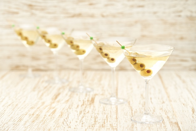 Пять стаканов алкогольного напитка на белом деревянном столе