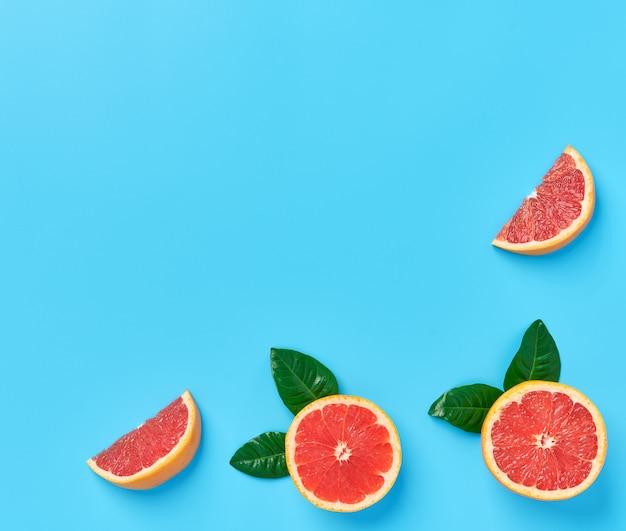 青色の背景にピンクグレープフルーツの熟した半分