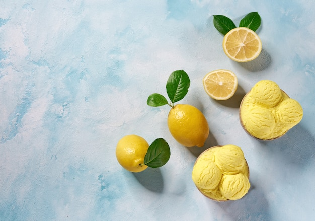 Две порции лимонного мороженого в бумажном стаканчике на мятном фоне цветов, вид сверху