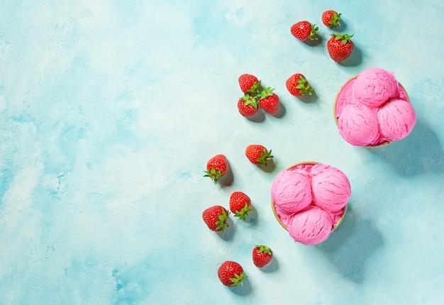 Две порции розовое мороженое в бумажном стаканчике на мятном фоне цветов, вид сверху