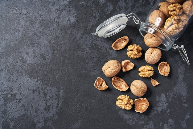 Грецкие орехи в открытой стеклянной банке на черном столе, крупным планом.