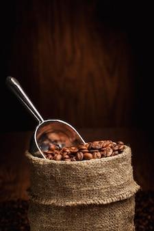 Мешок с кофе в зернах и совок
