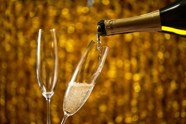 Лить шампанское в бокал на золотой стильный с золотыми кругами боке место для текста