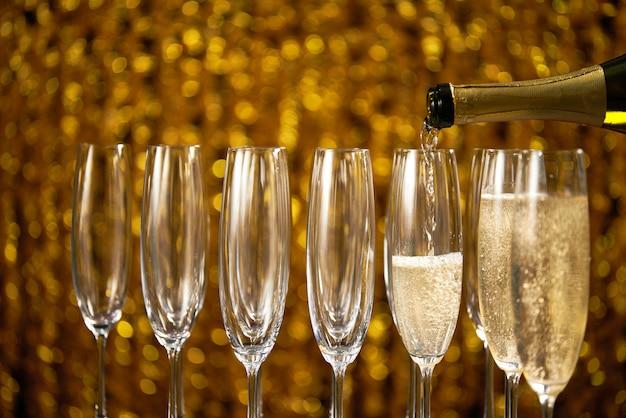 Наливая шампанское в бокал на свету,