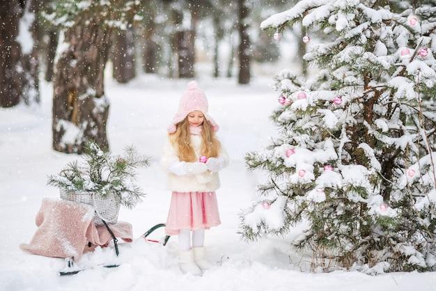 帽子とスカーフで愛らしい幼児ヨーロッパの子供女の子は美しいおもちゃでクリスマスツリーを飾る