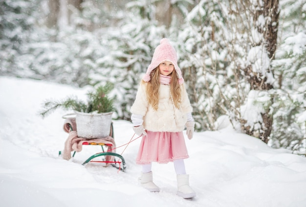 冬の森でかわいい女の子がそりで歩く