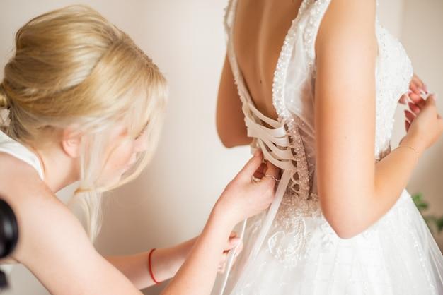 Утро невесты подруга помогает одеть платье. фото со спины. шнуровочный корсет