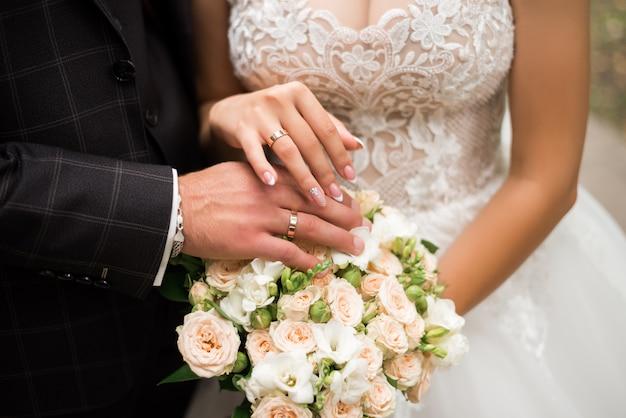 結婚式のブーケにリングで新郎新婦の手。結婚の概念