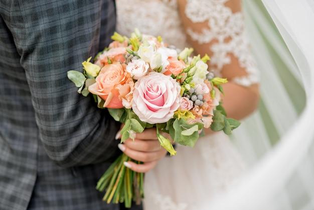 Жених и невеста держит красивый свадебный букет цветов