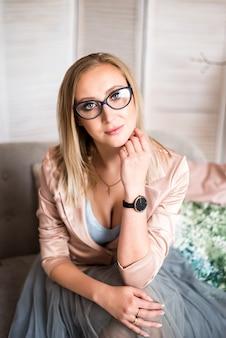 Красивая блондинка в очках с ручкой в руках на светлом фоне. бизнес-леди.