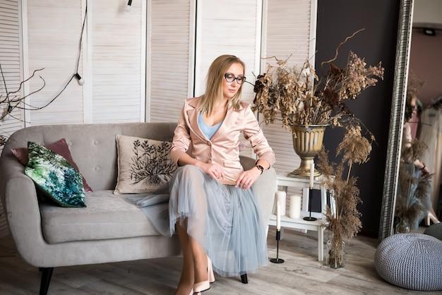 モダンな光の家で計画して、メモ帳とペンで座っている女性ブロンドの髪灰色のソファ。