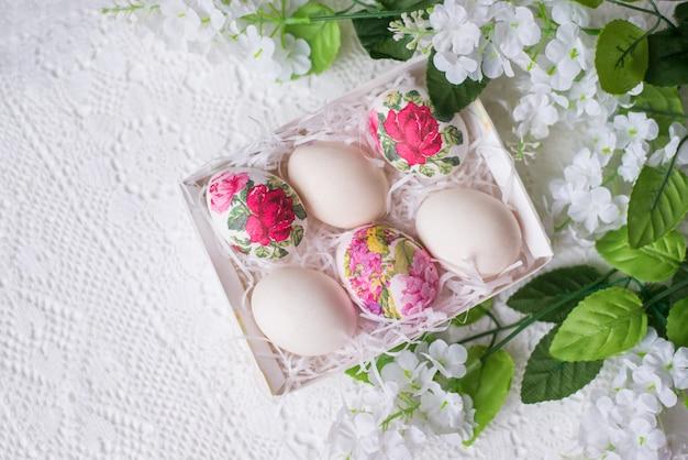 Пасхальные яйца с цветочным узором на белом фоне с цветами. пространство для текста