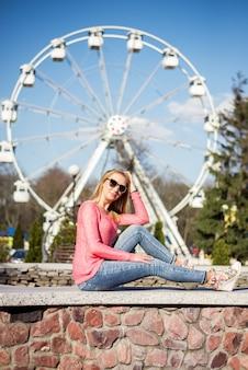 Молодая девушка сидит на фоне колеса обозрения