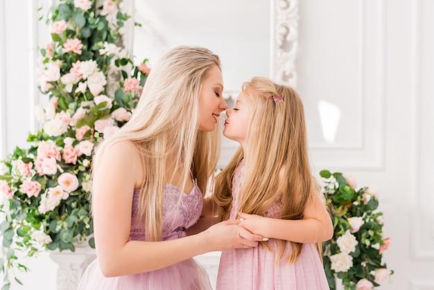 花の美しいインテリアでエレガントなドレスで母と娘の肖像画。