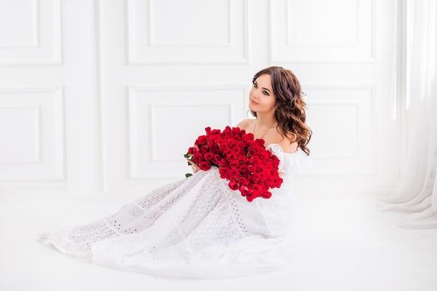 Красивая девушка с большим букетом красных роз в белом платье на свет. концепция праздников.