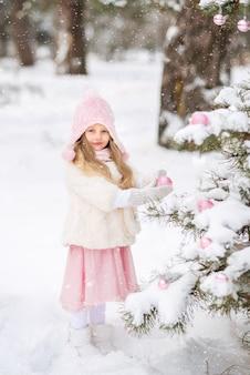 冬の森の白い毛皮のコートとピンクのふわふわのスカートでかわいい女の子は、クリスマスツリーをドレスアップします。ピンクのクリスマスのおもちゃ。