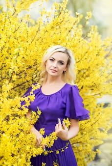 Крупным планом портрет девушки с профессиональным макияжем. красивая женщина в фиолетовом платье с цветущей форзиции.
