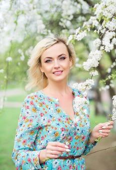 湖の上の公園でロマンチックな美しい女性は、開花木に立ち向かいます。花柄のドレスで美しい女性