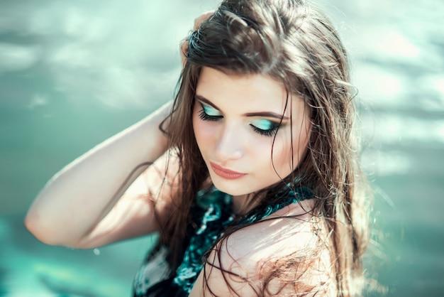 Портрет женщины в бирюзовом платье позирует на фоне моря, воды. сказочный образ морской принцессы, русалки с длинными волосами.