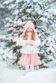Милая маленькая девочка в белой шубе и розовой пушистой юбке в лесу зимой одевает елку. розовые елочные игрушки.
