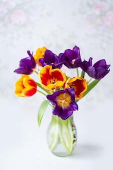 花瓶のマルチカラーのチューリップ。春の休日の花束