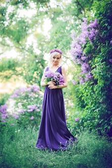 Красивая молодая женщина, в окружении фиолетовых цветов. женщина сидит в длинном платье с разрезом на фоне весеннего сада с сиренью