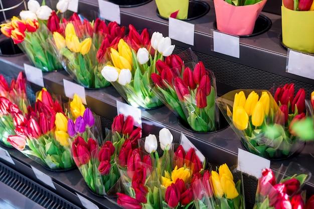 Конец-вверх много розовых, красных, желтых букетов тюльпана в цветочном магазине, цветочном рынке или магазине.