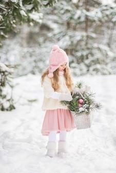 Сказка красивая девушка в белой шубе с белой большой корзиной с еловыми ветками в зимнем заснеженном лесу.