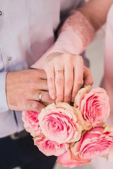 リングと新婚夫婦の手。ゴールドリング付きの新郎新婦の手の背景にウェディングブーケ
