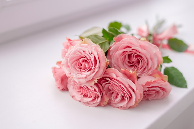 Цветочная рамка. нежная открытка с розовыми розами на мягком белом и розовом фоне. пространство для текста.