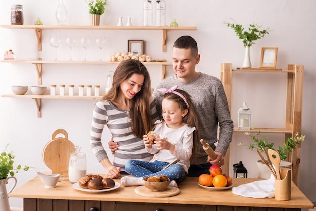 Милая маленькая девочка и ее красивые родители готовить еду и улыбаться во время приготовления пищи на кухне дома. замесить тесто на блины и рулеты