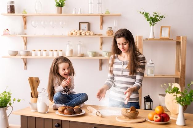 Милая маленькая девочка и ее красивая мама обсыпают тесто мукой и улыбаются во время выпечки