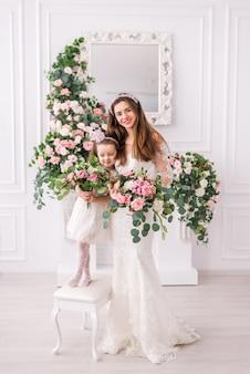 花と白いドレスの花嫁の母と娘