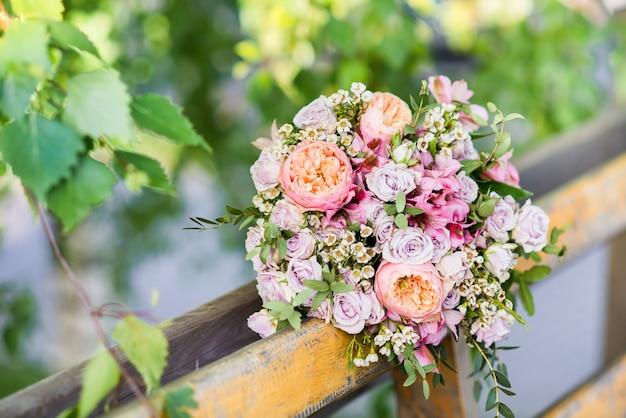 Красивый свадебный букет из розовых и бежевых роз на коричневой деревянной скамейке