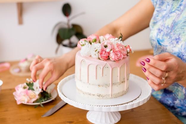 Крупный план женских рук, украшающих торт живыми цветами.