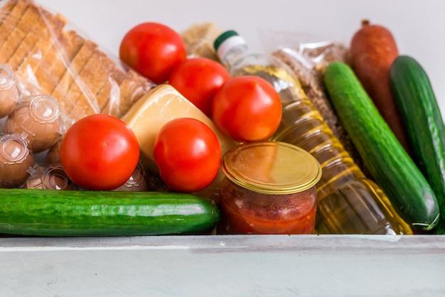 Ящик для пожертвований с едой. гуманитарная помощь во время пандемии коронавируса. коробка с предметами первой необходимости, макароны, крупы и овощи.