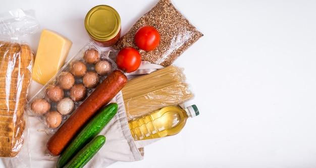Доставка еды, пожертвования. текстильная сумка с продовольственными запасами кризисного продовольственного снабжения на период карантинной изоляции на белом фоне