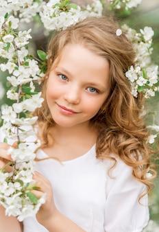春に咲く庭で美しい少女の肖像画。彼女の髪に白い花を持つかわいい赤ちゃん。
