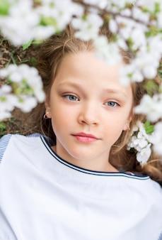 ブルーミングガーデンの美しいモデルの少女の肖像画。彼女の髪に白い花