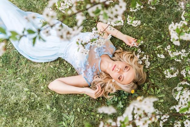 Красивая женщина в длинном платье лежит на траве в весеннем саду