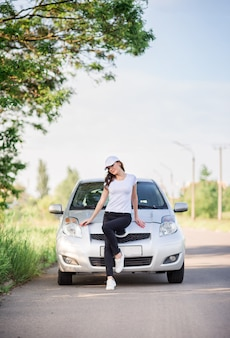 スポーツウェアと野球帽の女の子が道路上の車の近くに立っています。