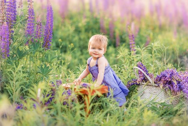 Маленькая девочка в сиреневый сарафан в окружении цветов в природе. ребенок стоит в траве