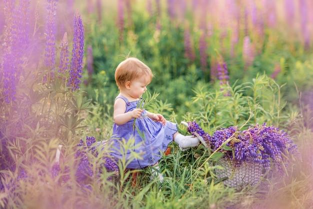 Маленькая девочка в сиреневый сарафан, сидя в природе. ребенок в цветах