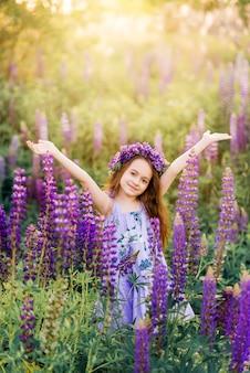 花の中で彼女の髪に花を持つ美しい少女。紫の花の子供と日当たりの良い夏の写真