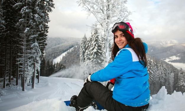 Молодая задумчивая женщина зимой в снежном лесу на вершине горы